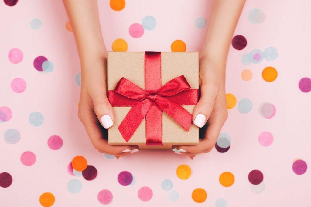 Poklon uvijen u papir sa crvenom mašnom